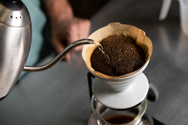 Maintain a consistent flow as you pour a minimum of five passes of water over the coffee grounds, being sure to go back and forth over the entire slurry.